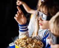 Flicka som pekar, medan hålla ögonen på filmen 3D med Arkivfoto