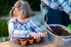 Flicka som planterar blommakulor Royaltyfria Bilder