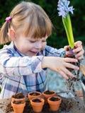 Flicka som planterar blommakulor Royaltyfria Foton