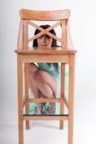 Flicka som poserar att sitta nära stol Arkivbild