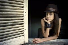 Flicka som poserar i ett öppet fönster Arkivbild