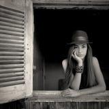 Flicka som poserar i ett öppet fönster Royaltyfri Bild