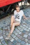 Flicka som poserar med den gamla spårvagnen Royaltyfri Foto