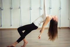 Flicka som preapring för flyg- yoga som öva - anti-gravitation med scarves arkivfoto