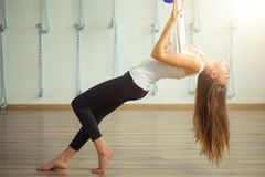 Flicka som preapring för flyg- yoga som öva - anti-gravitation med scarves royaltyfria foton