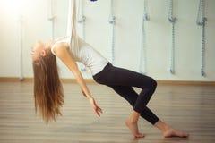 Flicka som preapring för flyg- yoga som öva - anti-gravitation med scarves royaltyfri foto