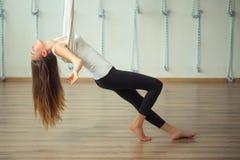 Flicka som preapring för flyg- yoga som öva - anti-gravitation med scarves arkivbilder