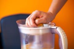 Flicka som pressar en apelsin med en elektrisk citrus juicer Royaltyfri Bild
