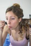 Flicka som rätar ut hennes hår och sätter på makeup Arkivfoton