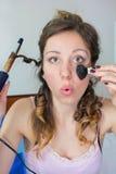 Flicka som rätar ut hennes hår och sätter på makeup Arkivfoto