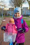 Flicka som rider en cykel med dockan Barnet rider en cykel Arkivbild
