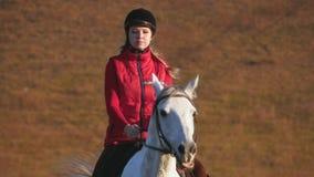 Flicka som rider en häst som galopperar på en äng långsam rörelse arkivfilmer