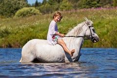 Flicka som rider en häst i en flod Arkivbild