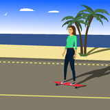 Flicka som rider en longboard på kusten Royaltyfria Foton
