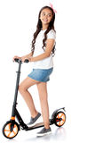 Flicka som rider en sparkcykel royaltyfri fotografi