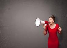 Flicka som ropar in i megafonen på kopieringsutrymmebakgrund Fotografering för Bildbyråer