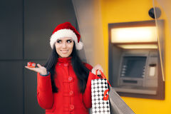 Flicka som rymmer den lilla gåvaasken, och shoppingpåsar som är främsta av en ATM Fotografering för Bildbyråer