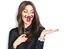 Flicka som rymmer den roliga mustaschen på pinnen och visar tom copyspace Royaltyfri Bild