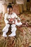 flicka som rymmer den små nyfödda siblingen Arkivfoto