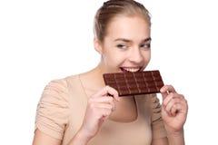 Flicka som rymmer den stora chokladstången i hennes tooths royaltyfri foto