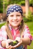 Flicka som rymmer den unga växten i händer Arkivbilder