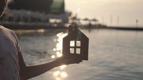 Flicka som rymmer det pappers- huset på stranden under solnedgång Folk, dröm, familj, fastighet och hem- begrepp Barndr?mmar arkivfilmer