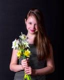 Flicka som rymmer en bukett av gula och vita påskliljor Arkivbild