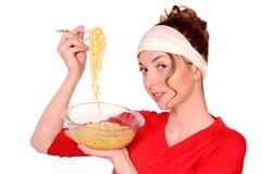 Flicka som rymmer en bunke av pasta fotografering för bildbyråer