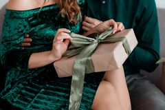 Flicka som rymmer en gåva i händer, kvinnor med gåvaasken i händer som slås in i dekorativt hantverkpapper royaltyfri foto
