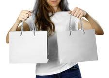 Flicka som rymmer en grå pappers- gåvapåse close upp Isolerad bakgrund arkivbild