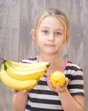 Flicka som rymmer en grupp av bananer och citronen Arkivfoto