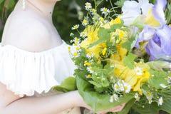 Flicka som rymmer en härlig bukett av blommor Arkivfoton