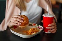 Flicka som rymmer en hamburgare, äter snabbmat och dricker cola arkivbild