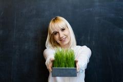 Flicka som rymmer en järnkruka med grönt gräs på en mörk bakgrund Royaltyfria Foton