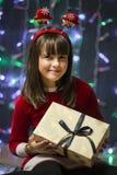 Flicka som rymmer en julgåvaask Arkivfoto