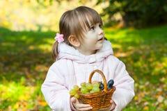 Flicka som rymmer en korg med druvor och äpplen arkivfoto