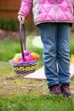 Flicka som rymmer en korg med påskägg royaltyfri foto