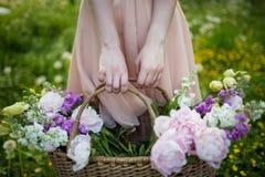 Flicka som rymmer en korg med sommarblommor Royaltyfri Fotografi