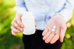 Flicka som rymmer en krus av piller i hennes händer, utomhus fotografering för bildbyråer