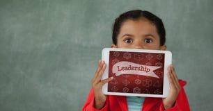 Flicka som rymmer en minnestavla med skolasymboler på skärmen Royaltyfri Bild