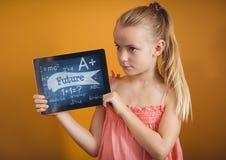 Flicka som rymmer en minnestavla med skolasymboler på skärmen Arkivbild