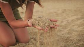 Flicka som rymmer en sand som tidsnedstegen till och med dina fingrar Begrepp f?r semester f?r sommarstrandferie lager videofilmer