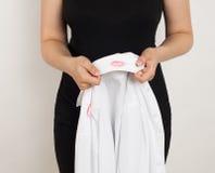 Flicka som rymmer en skjorta med avtrycken av läppstift Arkivbild