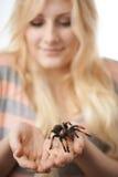 Flicka som rymmer en stor spindel på henne händer Arkivfoto