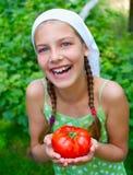 Flicka som rymmer en tomat Arkivfoto