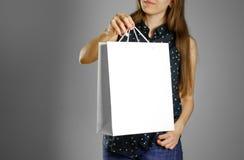 Flicka som rymmer en vit gåvapåse arkivbild