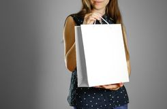 Flicka som rymmer en vit gåvapåse royaltyfria foton