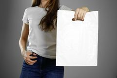 Flicka som rymmer en vit plastpåse close upp Isolerad bakgrund royaltyfri fotografi
