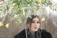 Flicka som rymmer ett blommaparaply i trädgård royaltyfria bilder