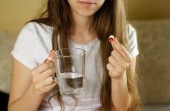 Flicka som rymmer ett exponeringsglas av vatten och preventivpillerar closeup royaltyfri bild